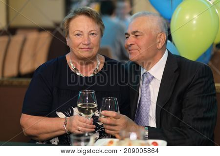 portrait of family elderly couple, man and woman on holiday holding glasses of wine, feast