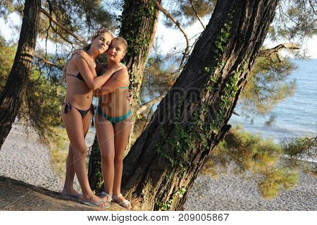 Two teenage girls hugging in bathing suits on beach, smiling