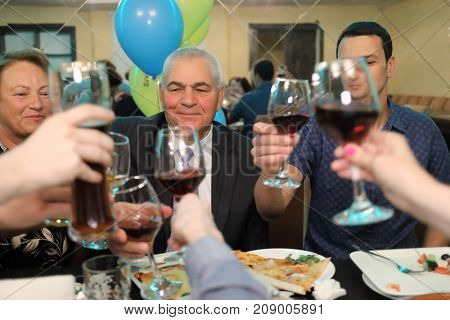 guests at table on anniversary, hands holding glasses and toasting, happy festive moment