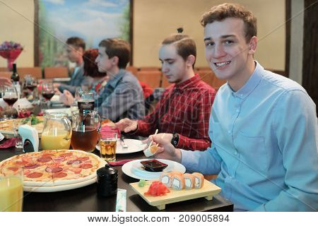 sitting guests invited to feast eat at table, young man in foreground eating rolls and smiling