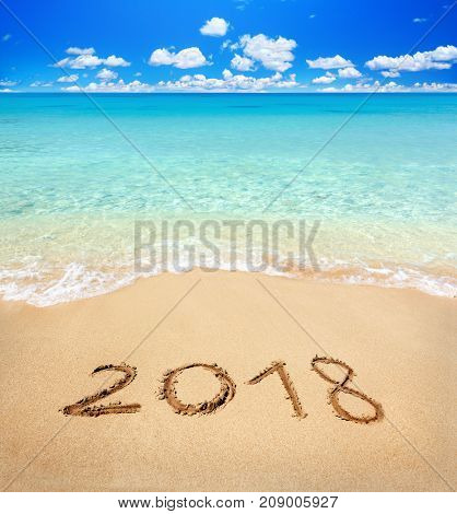 2018 written on sandy beach