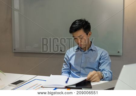 Business employee sneakily using phone in the meeting