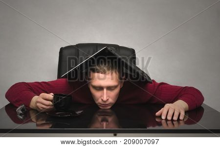 Student man tired of studying and sleeping on the school desk table with laptop computer above his head. Tired employee worker. Overworked businessman. Hard job.