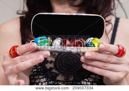 Woman's Hands Holding Tray With Many Various Colorful Rings