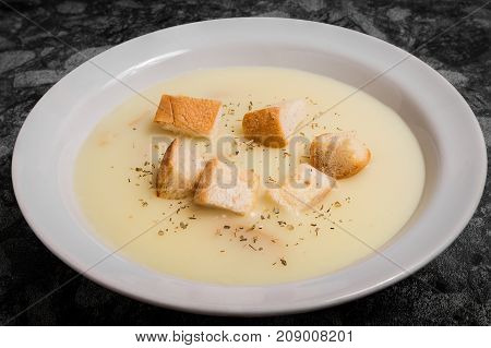 Mushroom cream soup with croutons and spices on a plate