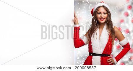 Smiling young woman dressed for Christmas showing a blank board