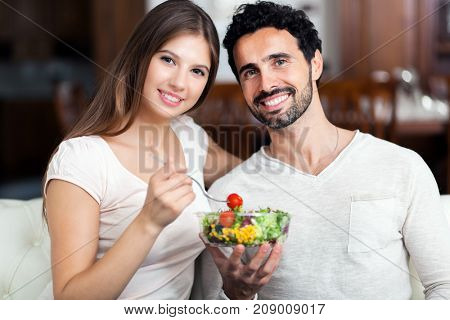 Happy couple eating a healthy salad