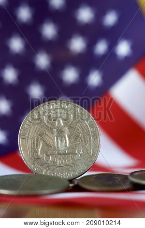 American quarter dollar coin with the US flag in the background.