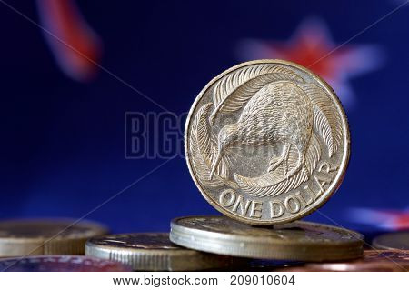 New Zealand dollar coin with the NZ flag in the background.