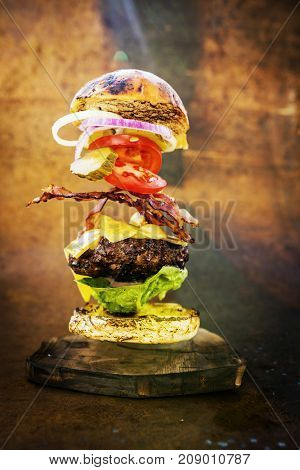 Hamburger with realistic flying ingredients. Tasty smoked grilled and glazed beef burger with lettuce, cheese and bacon on wooden table with copyspace.