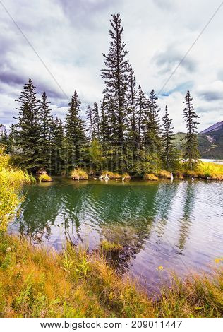 Magnificent journey through the Rocky Mountains of Canada. The wind creates a ripple on the lake water. Concept of active and ecological tourism