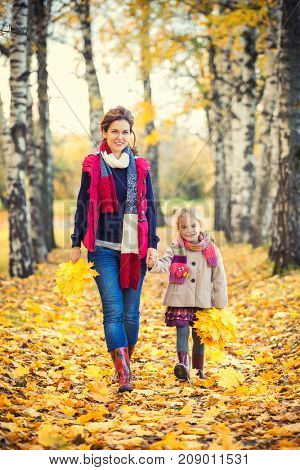 Smiling little girl and her mother enjoy walk in autumn park and play with bright autumn leaves