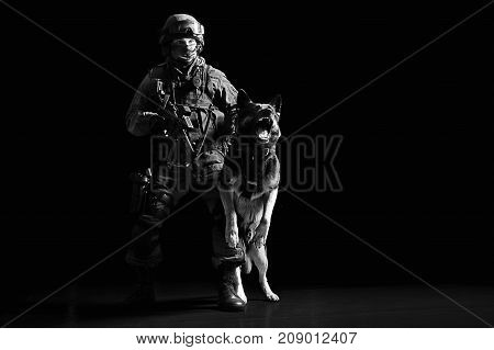 Armed Man In Military Uniform With A Machine Gun Restrains A Barking Service Dog