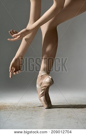 Wonderful ballerina is posing in the studio on the gray background. She stands on the toe and holds her arms next to the leg. Girl wears beige pointe shoes. Closeup. Vertical.
