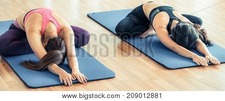 Women Doing Back Stretching Yoga In Fitness Gym