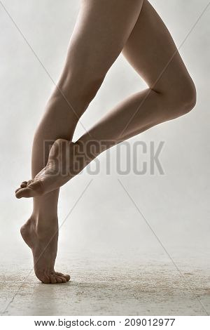 Beautiful ballerina is posing in the studio on the gray background. She stands on the right toe and holds left foot on the right leg. Closeup. Vertical.