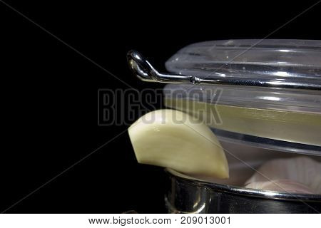 Garlic in a metal container on a black background