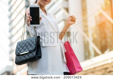 Woman With Shopping Bag Showing Phone Screen.