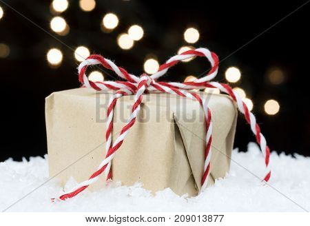 Handmade Paper Wrapped Vintage Gift Tied In Red And White Twine Sitting On Snow