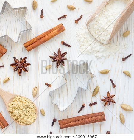 Christmas background with different spices flour and cookie cutters on a white wooden table top view square format