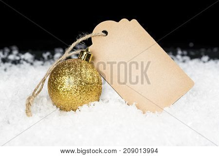 Blank Decorative Cardboard Tag And Golden Glittering Ornament Sitting On Snow, Black Background