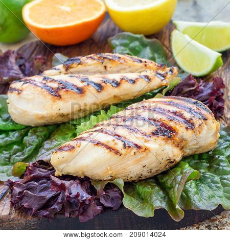 Grilled chicken breast in citrus marinade on salad leaves and wooden cutting board square format