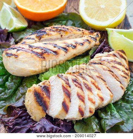 Grilled chicken breasts in citrus marinade on salad leaves and wooden cutting board square format