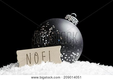 Black And Silver Ornament Sparkling In Light, Sitting On Snow Behind Simple Wooden Noel Sign