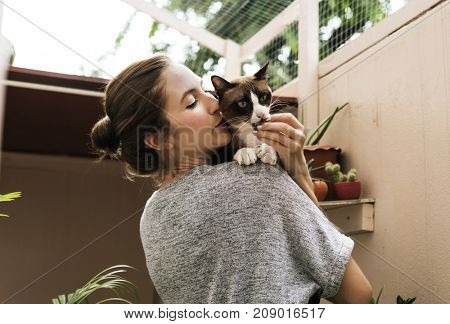 Woman holding and kissing her cat