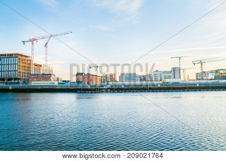 Dublin building boom illustrated in this early morning image across Liffey River an array of old wharf modern newer and underconstruction buildings with constructuction cranes across skyline. Ireland.