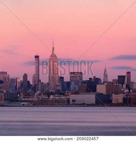 New York City midtown skyline with skyscrapers over Hudson River viewed from New Jersey at sunset