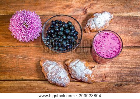 Croissants with sugar powder, berry smoothie in glass,  black currant and pink aster flower on wooden table. Romantic breakfast or snack.