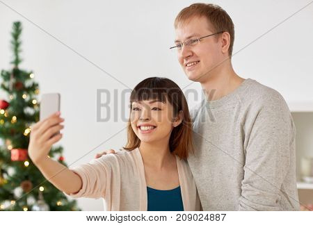 winter holidays, technology and people concept - happy mixed-raced couple taking selfie by smartphone home at christmas