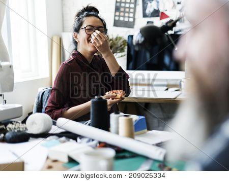 Cheerful fashion designer holding a pizza