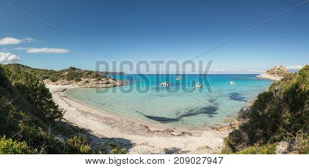 Panoramic view of several small boats moored in a calm bay with a translucent and turquoise Mediterranean sea by a small sandy beach off the rocky coast of the Desert des Agriates in Corsica