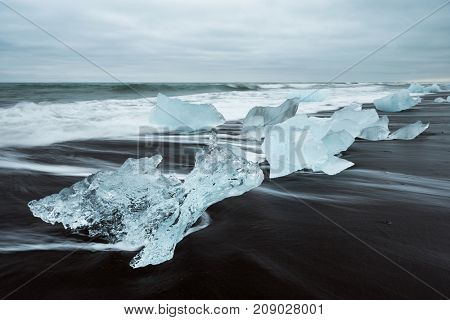 Icy beach in Iceland, Europe. Iceberg on the black volcanic sand on the Atlantic Ocean. Tourist attraction. Amazing landscape, cloudy day