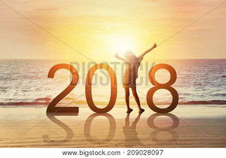 Happy new year card 2018.Silhouette of joyful young Asian girl hold hands breath fresh air on tropical beach with sunset or sunrise sky background. Happy kid watch rising sun stand in number 2018.