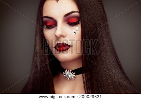 Halloween Vampire Woman portrait. Beautiful Glamour Fashion Sexy Vampire Lady with long dark Hair beauty make up and Costume