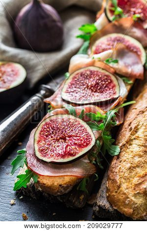Baguette sandwich with figs, prosciutto and arugula
