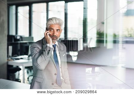 Mature businessman in gray suit in the office standing at the window holding smartphone making phone call. Shot through glass.