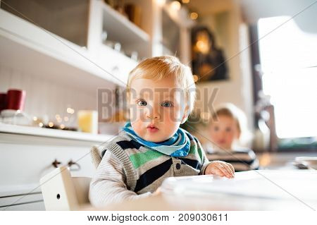 Cute baby boy sitting in highchair at Christmas time. Two small children in a kitchen.