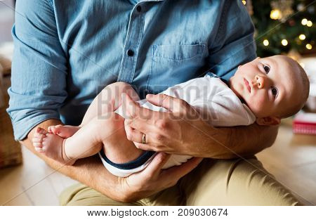Unrecognizable young father with baby son in front of Christmas tree. Man holding a baby in his arms.