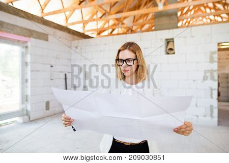 Beautiful young architect or a home owner looking at blueprints, controlling issues at the construction site.
