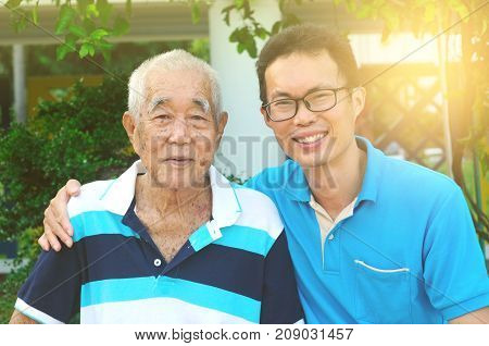 Happy asian family relaxing in the garden.Senior man smiling.