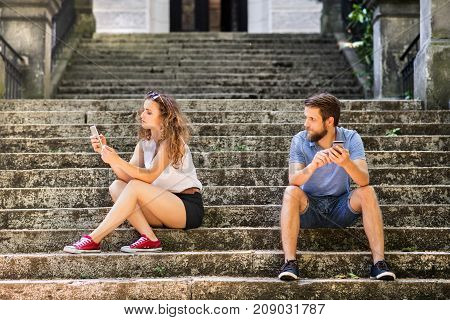 Beautiful young couple with smart phones sitting on stairs in town, texting. Sunny spring day.
