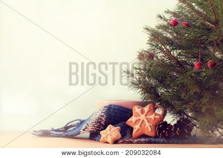 white mug in a blue scarf adorned with biscuits and cones stands under the tree / cozy Christmas morning