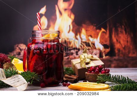 Cranberry and orange winter sangria near fireplace, Christmas decorated background. Copy space