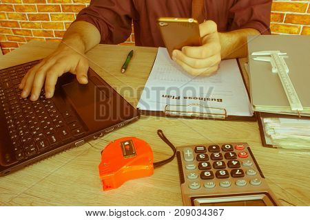 Photo businessman working on modern loft office. Man sitting wood table and using contemporary notebook texting message keyboard. Young Businessman Calculating Finance Bills In Office - Retro color