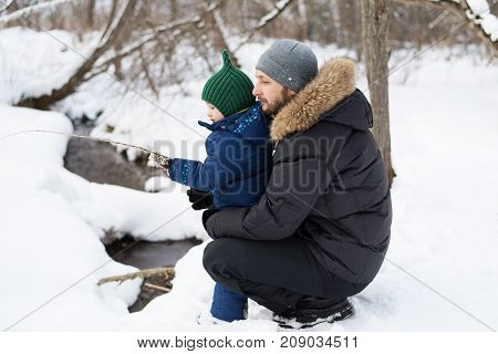 Father and child in a winter forest. They are fishing. Shot with soft focus.