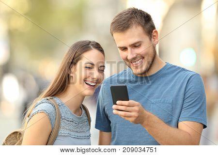Couple Enjoying Using A Smart Phone On The Street